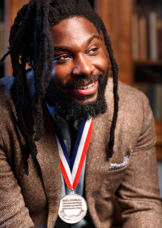 A photo of Jason Reynolds smiling with his medal.