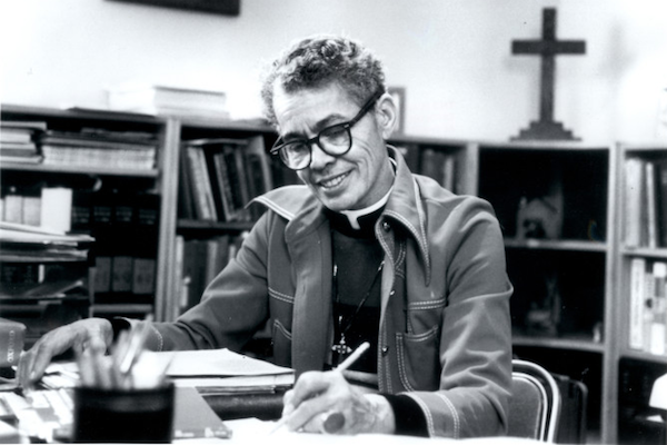 Black and white photo of Pauli Murray sitting at a desk in a library.