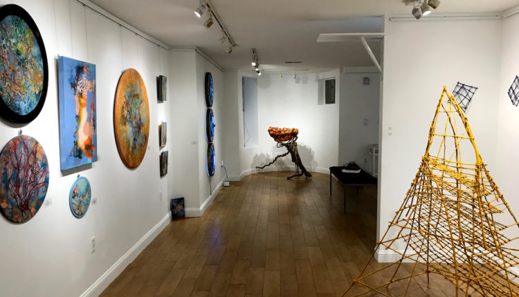 A gallery hallway featuring mixed media paintings and sculptures.