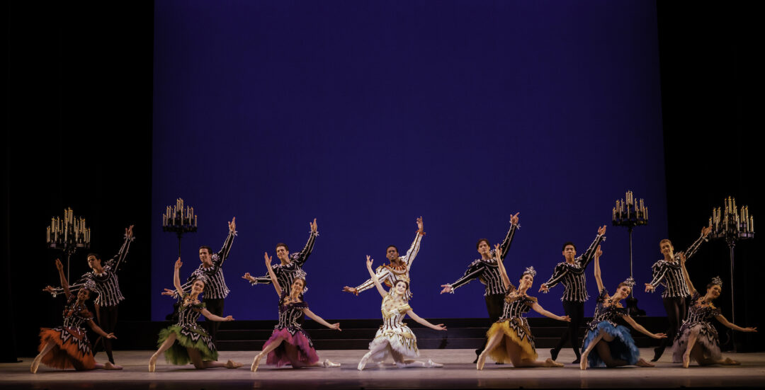 Eight male and eight female dancers pose in costume next to candelabras and a blue backdrop.